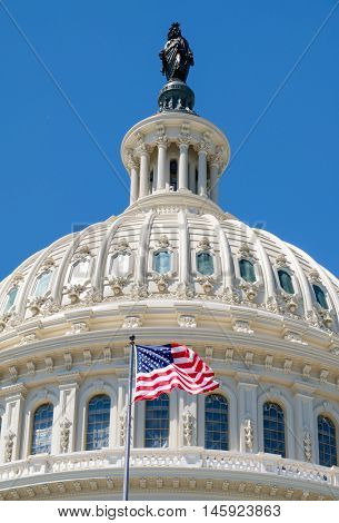 The US National Flag waves in fron of the Capitol building in Washington D.C.