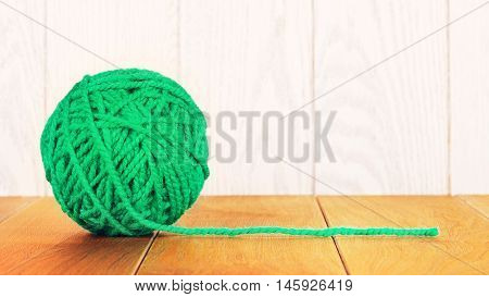 green yarn ball lying on wooden background