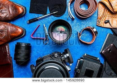 Photographer equipment and accessories over blue background. Flat lay
