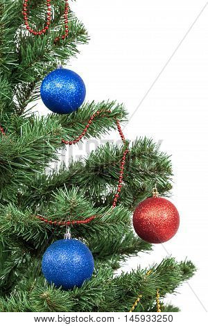 Christmas tree with red and blue baubles isolated on white background.
