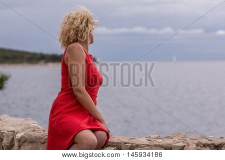 Beautiful curly blonde girl in red dress near of the sea