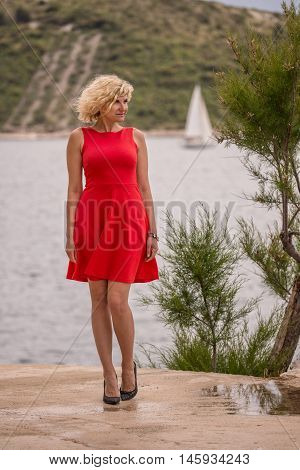Beautiful curly blonde girl in red dress is standing near of the sea