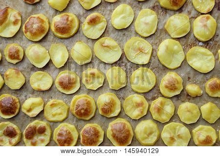 Slices of roast potatoes on a baking tray and paper.