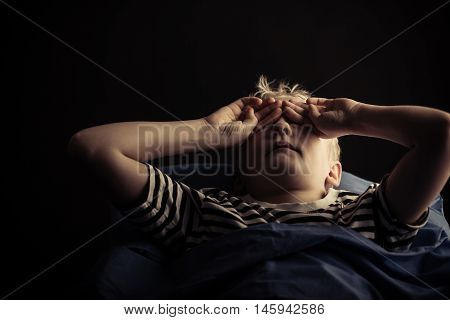Male Child Rubbing Eyes While Laying In Bed