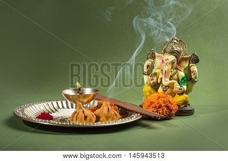 Hindu God Ganesha. Statue of Lord Ganesha. Pooja arrangement on green background.