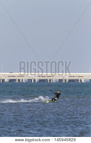 Tampa Bay Florida USA - February 28 2011: Stylish kiteboarder cranks across small chop off Fort De Soto