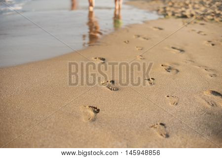 Footprints In The Sand. Human Footprints Leading Away From The Viewer. A Row Of Footprints In The Sa