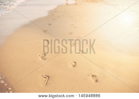 Children Footprints In The Sand. Human Footprints Leading Away From The Viewer. A Row Of Footprints