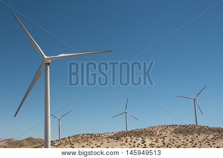 Windmills in desert landscape - Blue sky background