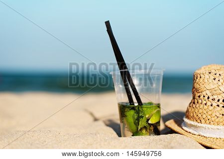 Mojito Cocktail On The Beach And Straw Hat. Blurred Beach Background With Copy Space. Sun, Sun Haze,