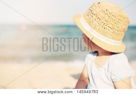 Baby Girl Child With Straw Hat And Blue Dress Looking At The Sea On A Sunny Day. Little Girl Sitting