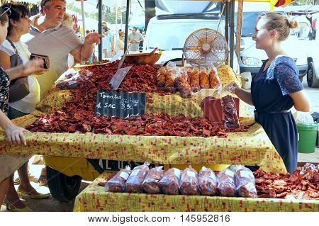 St Aygulf, Var, Provence, France, August 26 2016: A Stall Holder Selling Sun Dried Tomatoes From A P