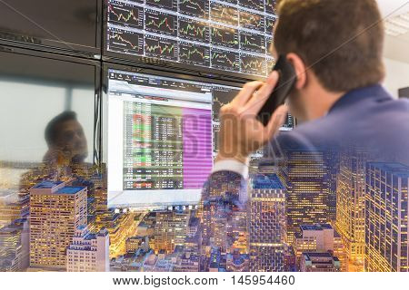 Businessman with cell phone trading stocks. Stock analyst looking at graphs, indexes and numbers on multiple computer screens. New Your city lights reflection in glass.