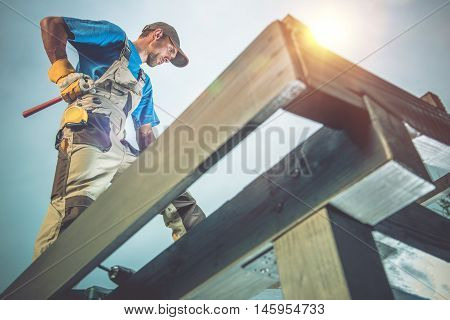 Wood Construction Works. Caucasian Worker on the Wooden Roof Construction.