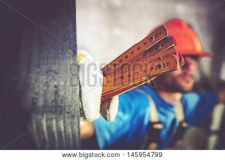 Construction Worker with Measuring Tool Closeup Photo. Home Construction Site Theme.