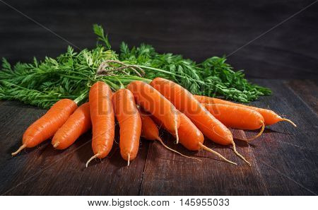 Bunch of fresh carrots vegetables with green leaves on rustic wooden background