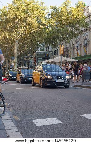 Barcelona Spain - July 23 2016: Taxi car goes by Ramblas avenue in Barcelona City