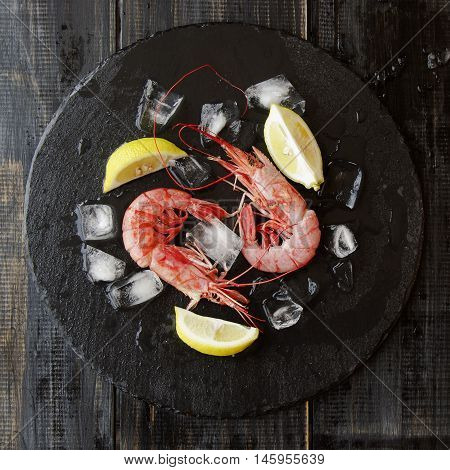 Two raw prawns with lemon and ice cubes on a blackboard selective focus