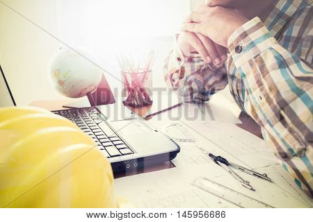 Architect With Construction Plan In Office