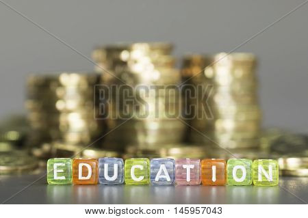 Close up Education text beside spilled gold coins