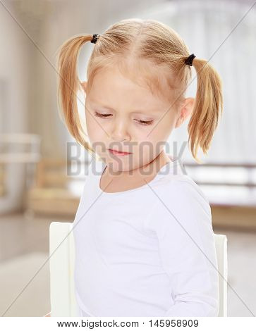 Distressed small, blonde girl with white t-shirts without a pattern.The concept of pre-school education of the child among their peers . in gaming room with a large arched window.