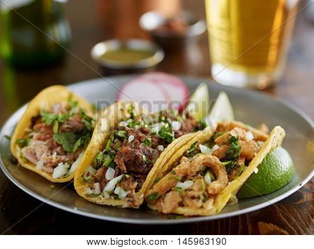 plate of mexican street tacos garnished with cilantro and onion