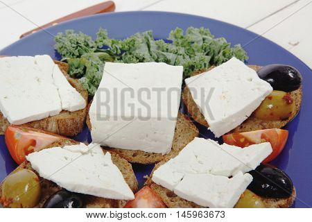 white feta greek cheese sandwich rye bread on blue plate with black spain olives tomatoes and cutlery over retro wooden table