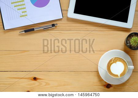 Office desk table with blank screen tabletpenanalysis chart and cup of coffee .Top view with copy space.Office desk table concept.Office supplies and gadgets on desk table.