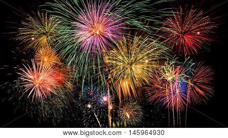 Colorful firework celebration on dark night sky background. Beautiful fireworks show on clear night sky.