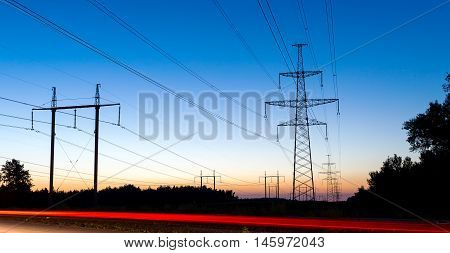 Pylons and electricity power lines at night with traffic lights in front