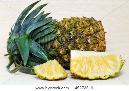 Fresh Pineapple With Slices Isolated On Wood