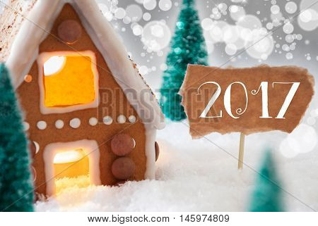 Gingerbread House In Snowy Scenery As Christmas Decoration. Christmas Trees And Candlelight For Romantic Atmosphere. Silver Background With Bokeh Effect. English Text 2017 For Happy New Year