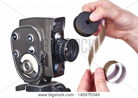 Retro Mechanical Movie Camera And Film Strip In Hands Operator