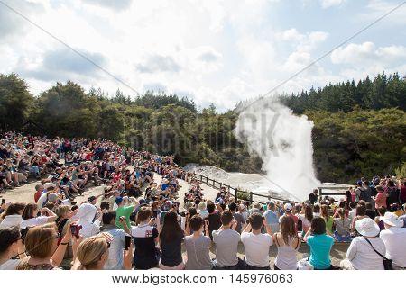Rotorua, New Zealand - February 25, 2015: Tourists watching the eruption of Lady Knox geyser in Wai-o-Tapu National Park