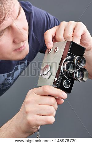 Retro Mechanical Movie Camera In Hands Of Man Isolated