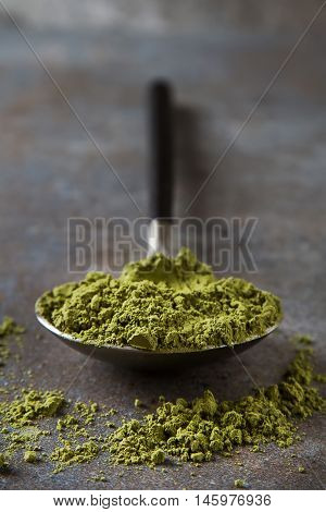 Matcha Tea On A Spoon With Black Handle. Gray Background.