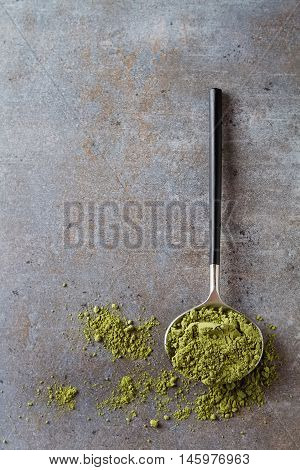 Matcha Tea On A Spoon With Black Handle. Gray Background. Top Vi