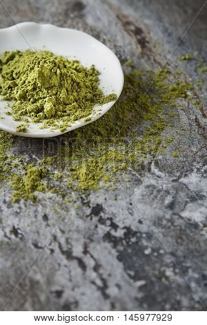 Matcha Tea On A Small White Plate. Gray Background. Top View
