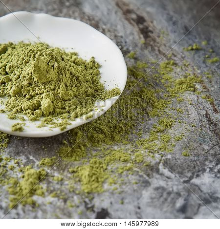 Matcha Tea On A Small White Plate. Gray Background. Top View. Sq