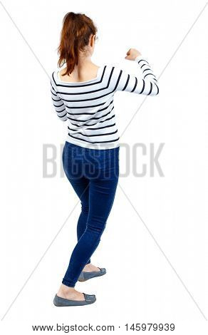 back view of woman funny fights waving his arms and legs. Girl in a striped sweater fights with fists.