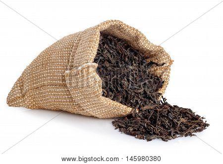 Black tea scattered of burlap bag isolated on white background. Black tea. Dry leaves of tea scattered of sack isolated on white. Scattered leaves of tea