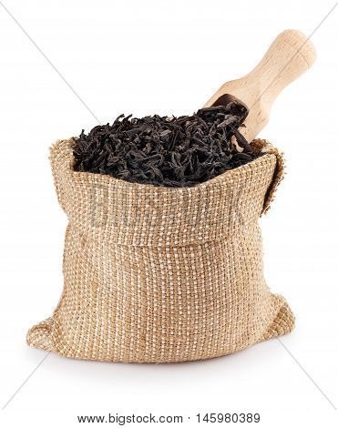 Black tea with wooden scoop in burlap bag isolated on white background. Black tea. Dry leaves of tea in sack isolated on white