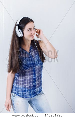 portrait of girl listening music wearing headphones with white wall background. Woman with headphones listening music. Teenager girl on white background. Cheerful young woman listening music with headphones.