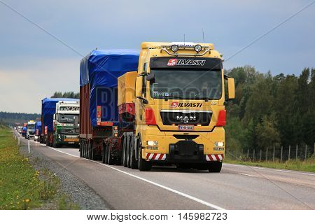 ORIVESI FINLAND - SEPTEMBER 1 2016: Yellow MAN V8 semi truck hauls wide load in convoy of four exceptional road transports of industrial objects.