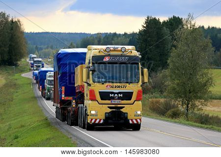 JAMSA FINLAND - SEPTEMBER 1 2016: Yellow MAN V8 semi truck hauls wide load first in convoy of four exceptional road transports of industrial objects.