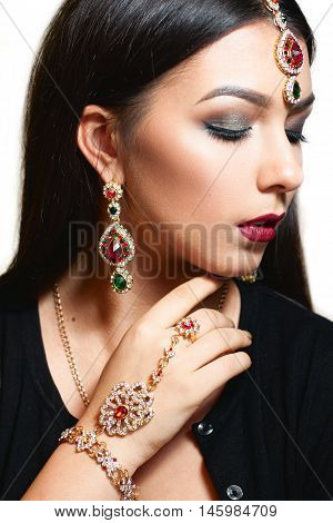 Gorgeous woman with luxurious jewelry close-up. Portrait of beautiful indian princess with ceremonial makeup and finery. Luxury, wealth, pleasure concept