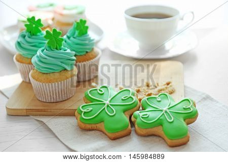 Tasty cupcakes and cookies on table. Saint Patrics Day concept