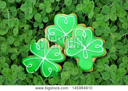 Decorative cookies on clover leaves. Saint Patrics Day concept