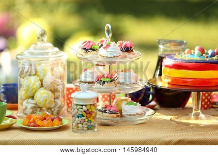 Table with birthday sweets and cake, outdoor
