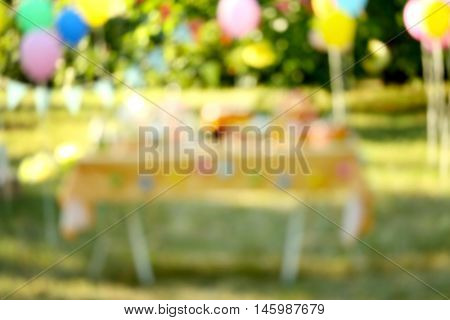 Birthday table in yard on blurred background